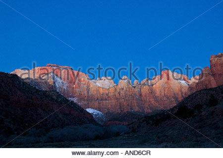 I picchi che comprendono le torri della Vergine nel Parco Nazionale di Zion, Utah sono illuminati da alpenglow appena Foto Stock