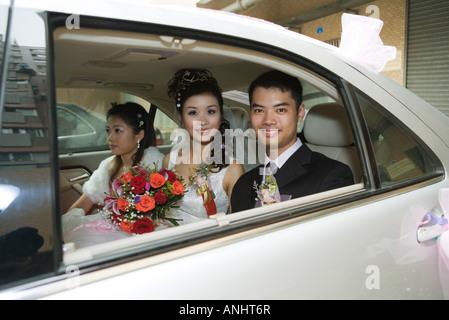 Sposa e lo sposo in auto con damigella, sorridente in telecamera Foto Stock