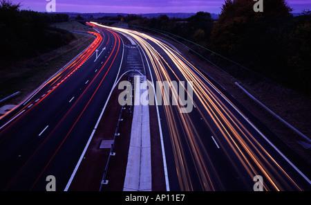Sentieri di luce sinistra del traffico in corrispondenza di una strada a doppia carreggiata di giunzione a crepuscolo Foto Stock