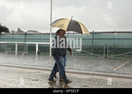 Due persone che camminano in una tempesta di pioggia lungo una strada in Inghilterra Foto Stock
