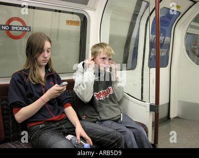 Ragazzo e una ragazza sul tubo in treno a Londra nel proprio piccolo mondo elettronico Foto Stock