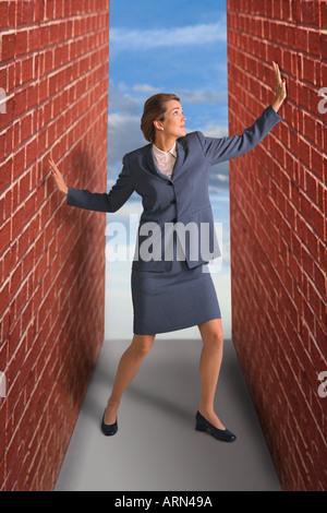 Donna intrappolata tra le pareti in mattoni Foto Stock