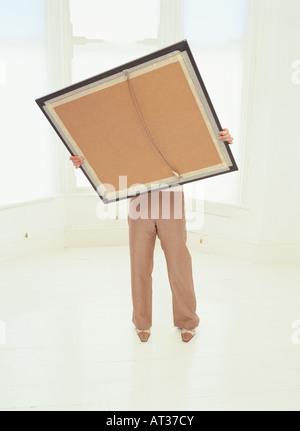 Una donna che mantiene una grande cornice immagine Foto Stock