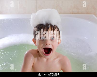 Bambino con divertenti look sorpreso in vasca con bolle sulla testa. Bagno di bolle. Foto Stock