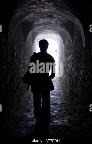 Un uomo cammina verso il basso una Sala nel castello di Elmina su un tour dell'ex schiavo fortezza Foto Stock