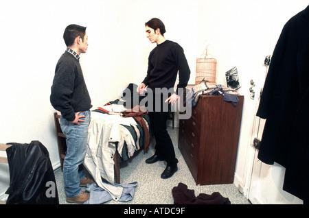 Maschio francese adolescenti coinquilini ragazzi sostenendo in camera da letto, uno asiatico, uno caucasico Cramped Foto Stock