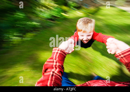 Ragazzo di 3 anni di essere filata intorno da papà Foto Stock