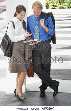 Due imprenditori all'esterno guardando i personal digital assistant Foto Stock