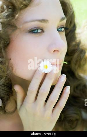 Giovane donna azienda fiore in bocca, cercando lontano, close-up Foto Stock