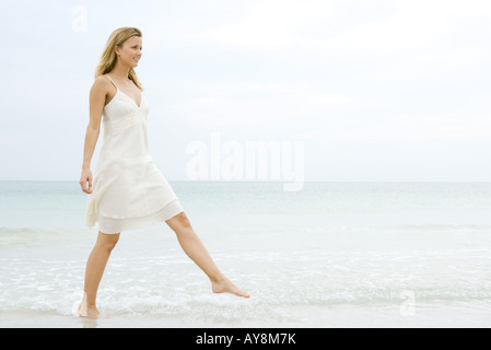 Giovane donna in sundress prendendo grande passo come si cammina in acque poco profonde sulla spiaggia a piena lunghezza Foto Stock
