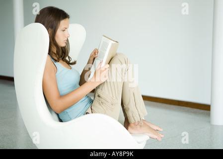 Ragazza adolescente seduto in poltrona, libro, vista laterale Foto Stock