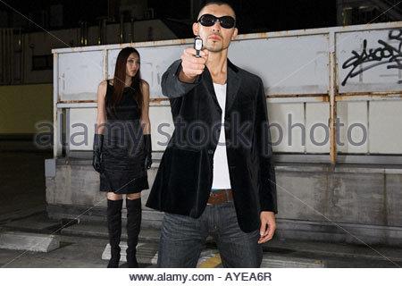 Uomo giapponese puntando la pistola in telecamera Foto Stock