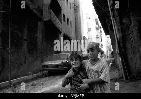 Ragazzi giocare in una scarsa backstreet abbandonati a sinistra dalla lunga guerra civile a Beirut, Libano Foto Stock