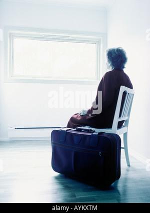 Donna anziana seduta nella stanza vuota con la valigia Foto Stock