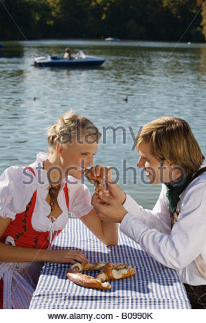 Coppia giovane nel tradizionale costume bavarese, mangiare Prezel, Monaco di Baviera Foto Stock