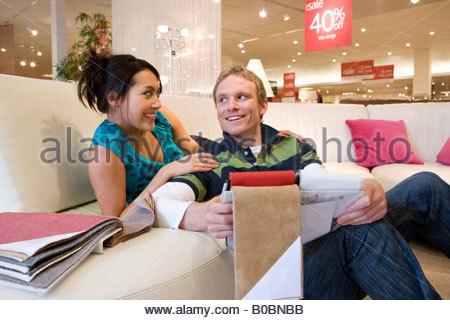 Coppia giovane esaminando campioni di tessuto in negozio, donna sul divano, sorridente Foto Stock