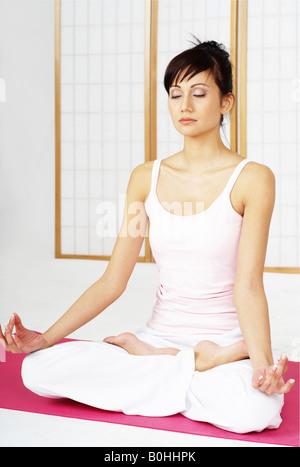 Giovane donna relax e meditazione seduti con le gambe incrociate Foto Stock
