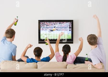 Amici guardare il calcio in tv Foto Stock