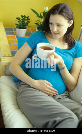 Donna incinta di bere una tazza di tè alle erbe Foto Stock