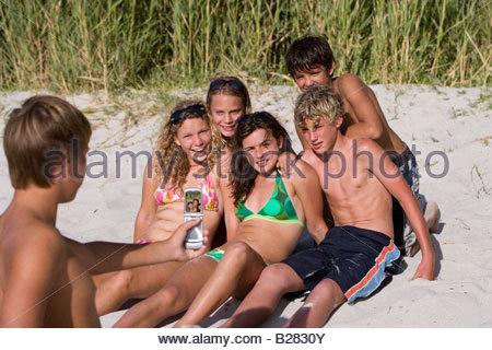 Ragazzo adolescente (14-16) prendendo fotografia di amici sulla spiaggia con il telefono cellulare, sorridente Foto Stock