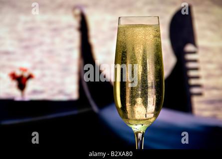 Bicchiere di spillata di fresco spumante, con le gondole venete dietro. Venezia Italia Foto Stock