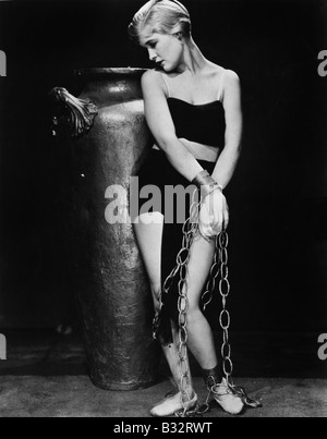 Donna incatenato davanti ad un grande vaso Foto Stock