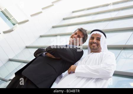 Due imprenditori in piedi all'aperto da edificio (alta chiave/messa a fuoco selettiva) Foto Stock