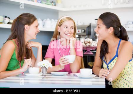 Tre giovani donna seduta al tavolo e bere il tè Foto Stock