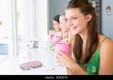 Tre giovani donne avente una bevanda fresca in una caffetteria Foto Stock
