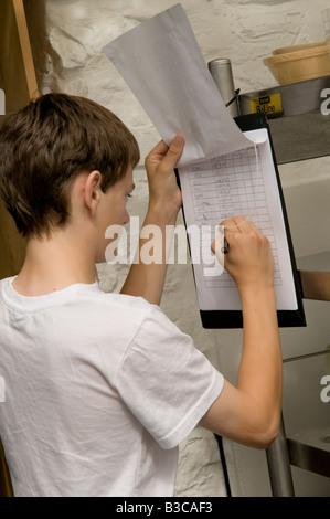 Giovane ragazzo adolescente impiegato in vacanza estiva job, riempimento nelle sue ore di lavoro su timesheet in Foto Stock