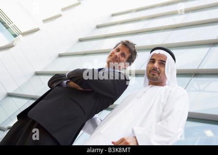 Due proprietari in piedi all'esterno mediante la costruzione di sorridente (alta chiave/messa a fuoco selettiva) Foto Stock