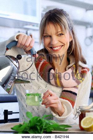 Donna preparare un bicchiere di tè alle erbe con succo di limone tenendo un bollitore d' acqua in mano Foto Stock