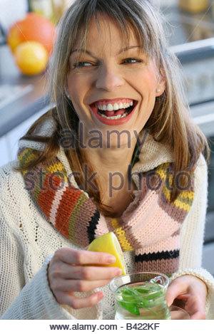 Donna preparare un bicchiere di tè alle erbe con succo di limone seduta in cucina Foto Stock