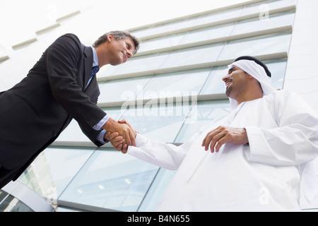 Due proprietari all'esterno mediante la costruzione di una stretta di mano e sorridente (alta chiave/messa a fuoco Foto Stock