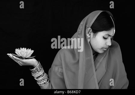 Donna indiana offre un Nymphaea ninfea tropicale fiore in un sari. Monocromatico Foto Stock