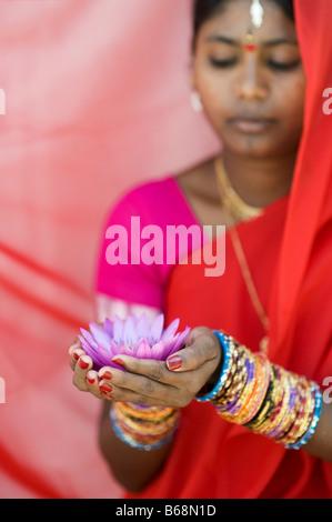 Donna indiana offre un Nymphaea ninfea tropicale fiore in un sari rosso. Andhra Pradesh, India Foto Stock