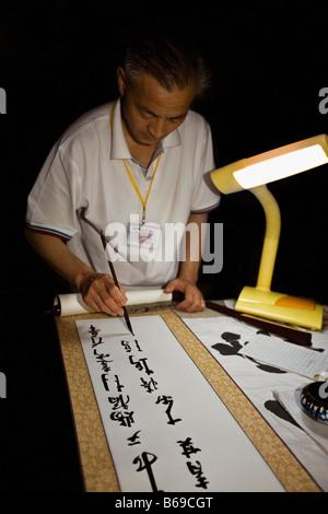 Uomo maturo Fare calligrafia, Tempio di Confucio, Qufu, Provincia di Shandong, Cina Foto Stock