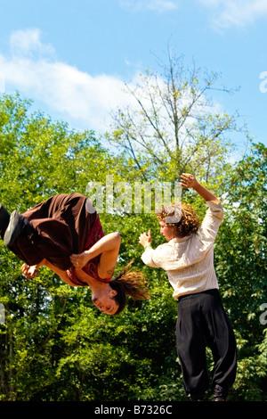 Immagine di due uomini vestiti in stile gitano abbigliamento facendo acrobazie dal dorso dei cavalli Foto Stock