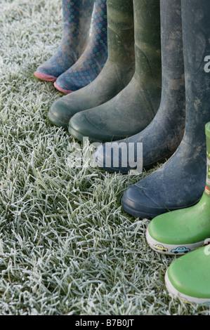 Una lineup di una famiglia di stivali da pioggia a sinistra su alcuni frosty erba verde che offre un immagine concettuale Foto Stock