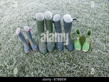 Una lineup stivali da pioggia a sinistra su alcuni frosty erba verde che offre un immagine concettuale che descrive Foto Stock