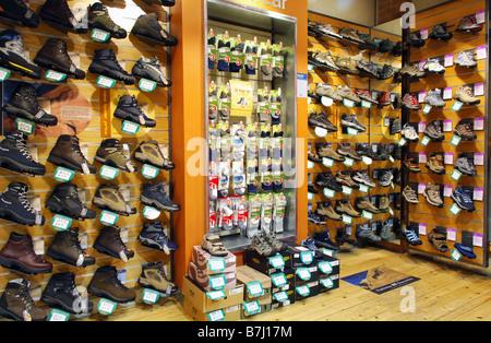 Una parete di visualizzazione di diversi Stivali di arrampicata e le calze per la vendita in un negozio specializzato Foto Stock