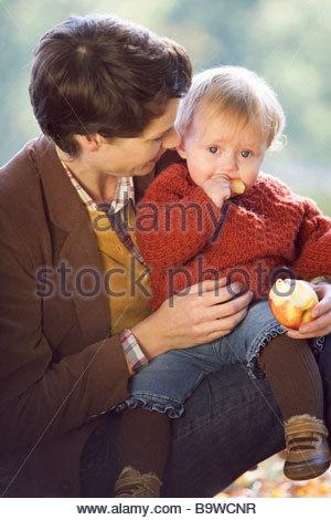 Una giovane madre sorridente al suo bambino mangiare un Apple Foto Stock
