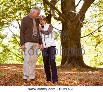 Una coppia senior tenendo le mani nel periodo autunnale Foto Stock