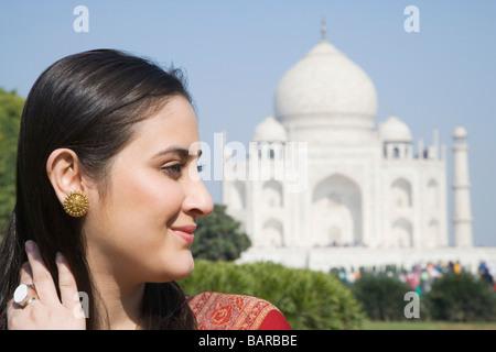 Close-up di una donna sorridente con un mausoleo in background, Taj Mahal, Agra, Uttar Pradesh, India Foto Stock