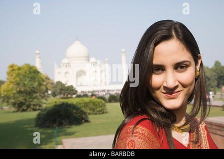 Ritratto di una donna sorridente con un mausoleo in background, Taj Mahal, Agra, Uttar Pradesh, India Foto Stock