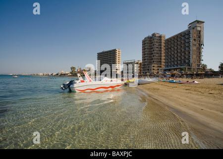 Barche sulla spiaggia di Varosha con le rovine di abbandono di alberghi in background, città fantasma, Famagosta, Foto Stock