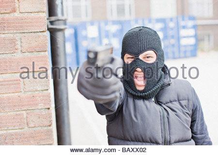 Uomo in pelle maschera pistola di contenimento Foto Stock