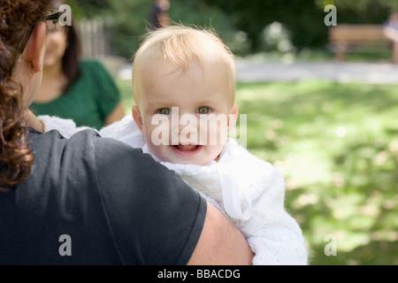 Una madre che porta la sua bambina, al di sopra della spalla Foto Stock