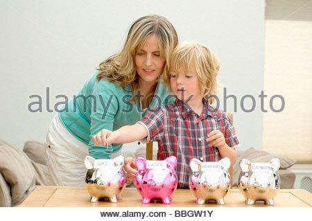 Madre e figlio mettendo coin salvadanaio, Den Haag, Paesi Bassi Foto Stock