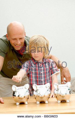 Padre e figlio mettendo coin salvadanaio, Den Haag, Paesi Bassi Foto Stock
